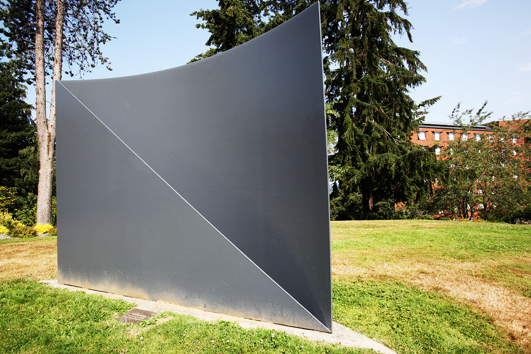 Metal sculpture, shaped and pointed like the tip of an arrow. Flat panes of metal that come together with a sharp point at the tip. It rests in the center of a grassy lawn creating dark shadows behind where the sun hits.