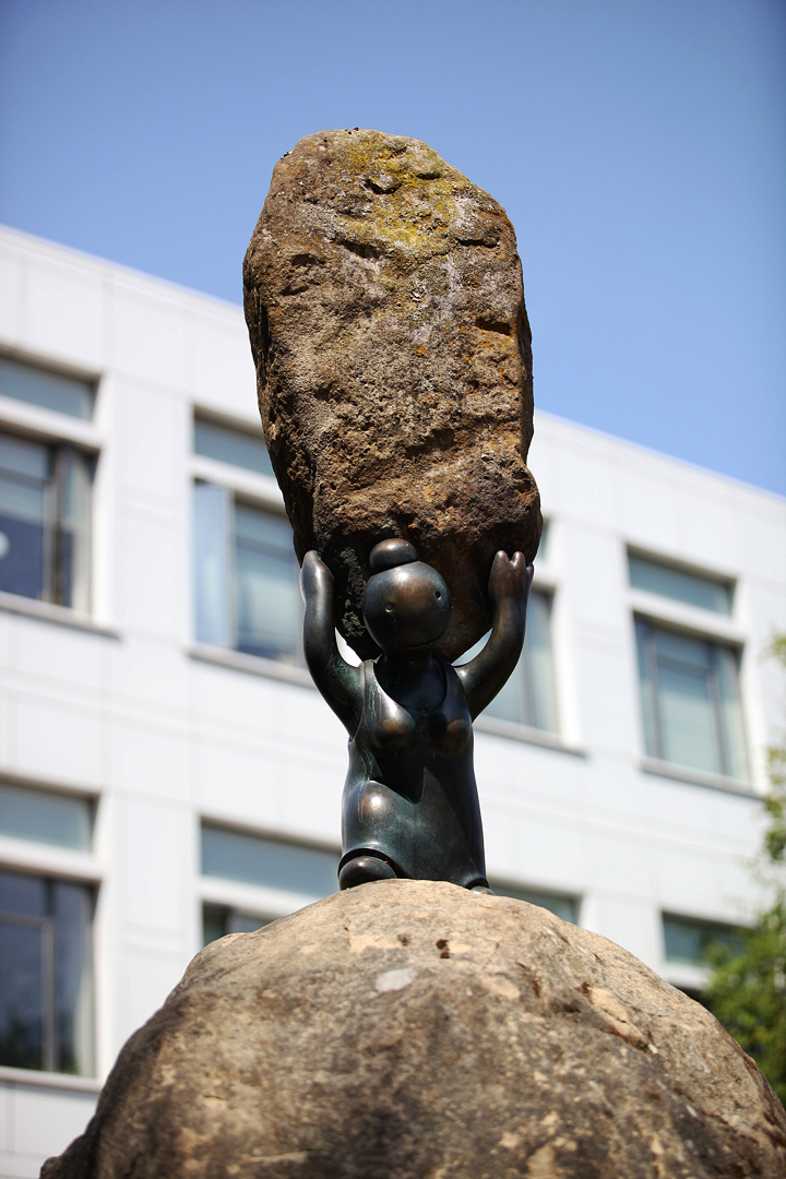 bronze sculpture of small stylized person carrying a heavy rock over its head. The rock is real