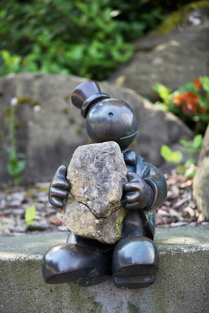 bronze sculpture of small stylized person carrying a heavy rock in both hands. The rock is real