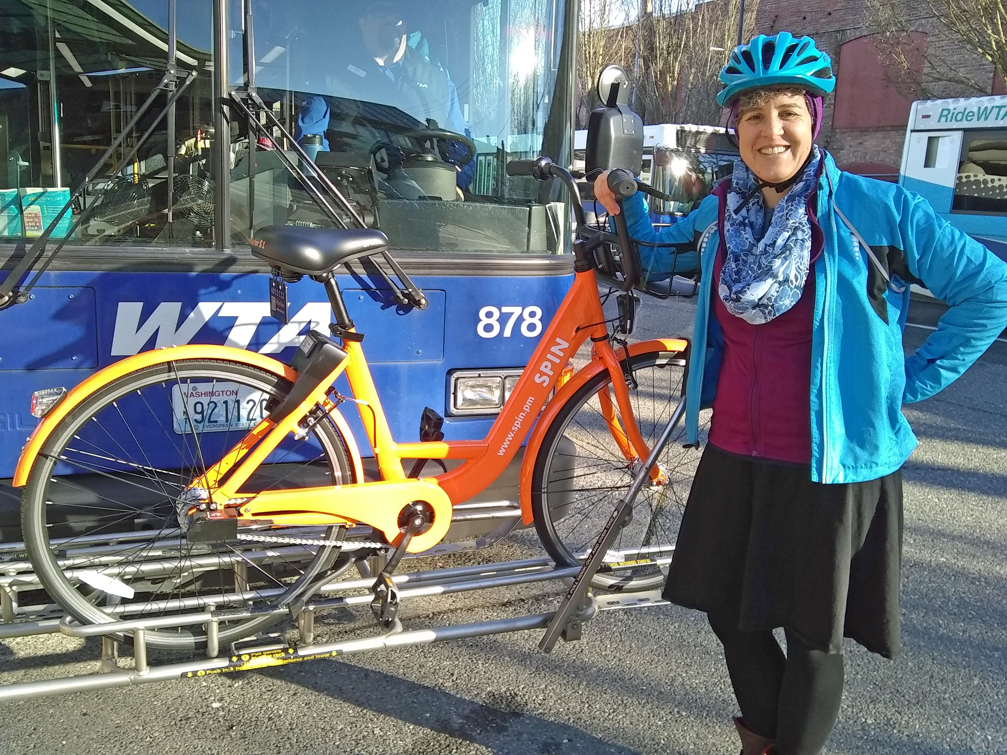Jillian Trinkaus standing in front of a bike on a rack in front of a WTA bus