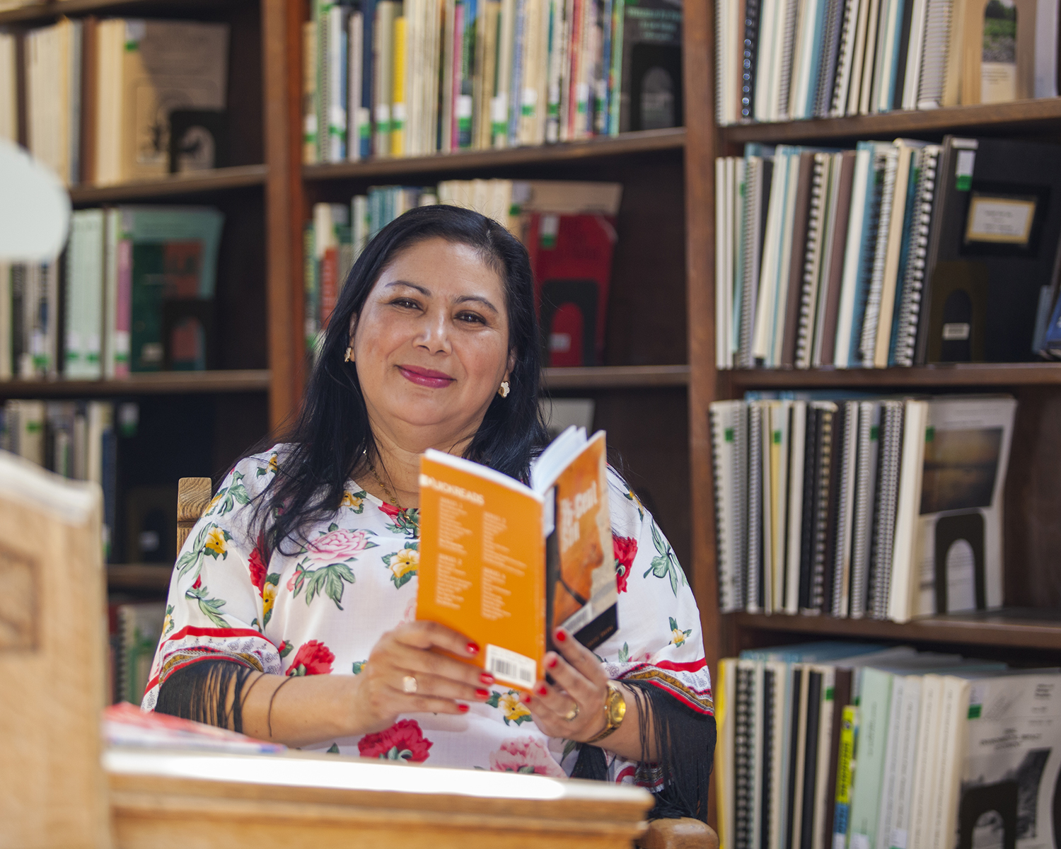 Blanca Granados de Cruz facing the camera while sitting at a desk with a book in her hands in the Wilson Library Reading Room
