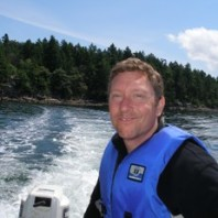 Photo of Colin Grier on a boat with the water and a forested hillside in the background.