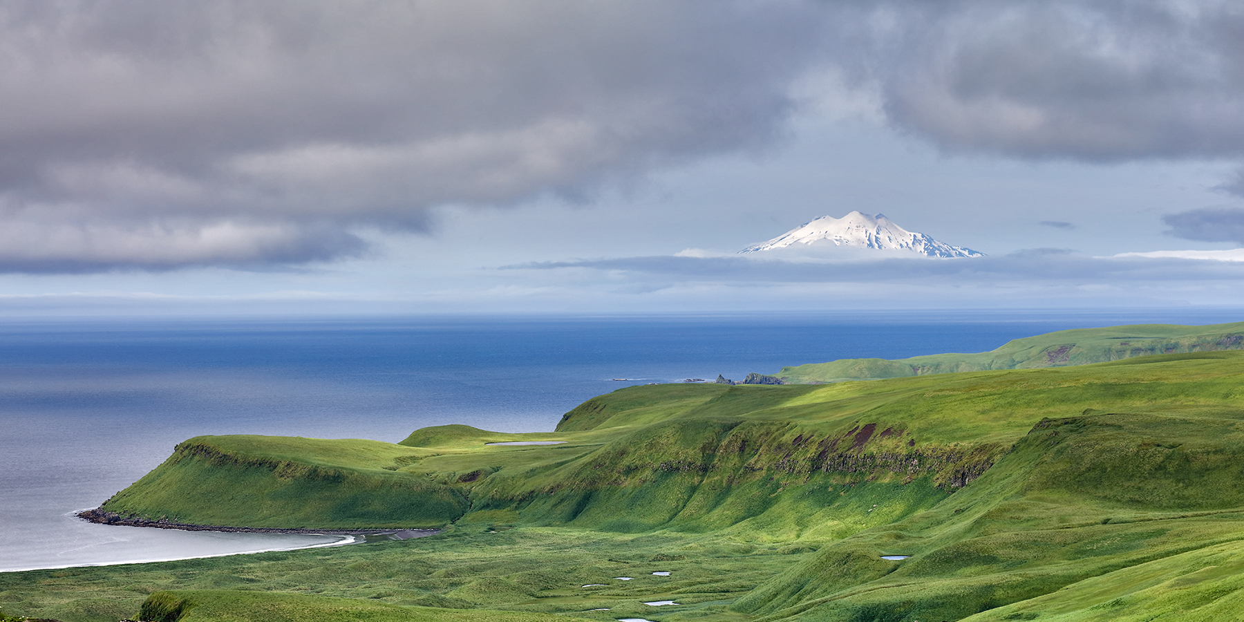 Gareloi Island and its massive volcano loom across the Bering Sea from Tanaga Island in the Aleutians. Photo by Eric DeChaine.