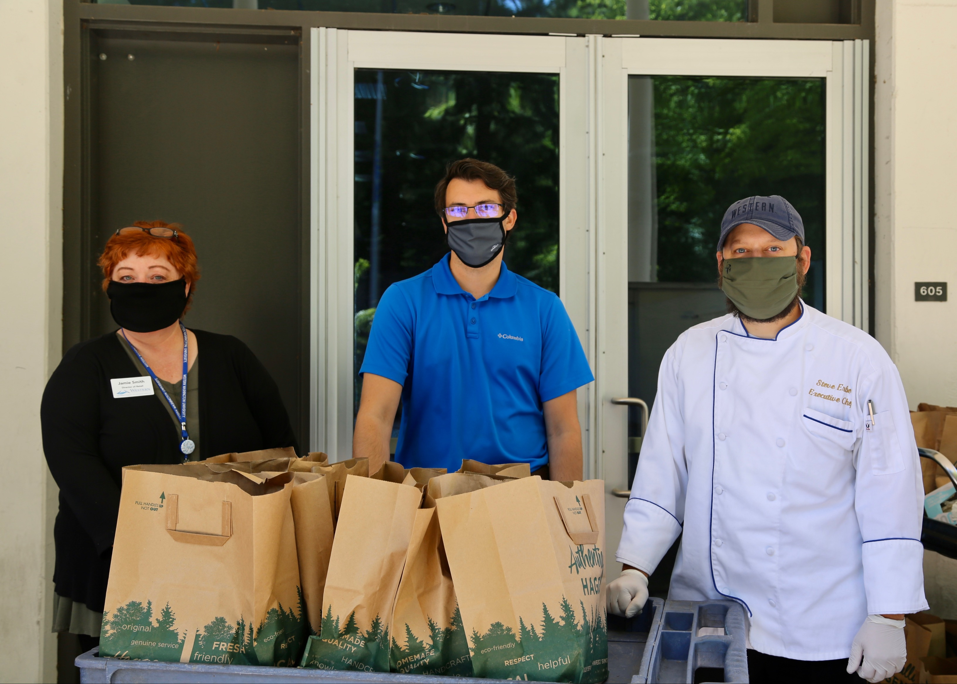 Jamie Smith, Jeremy Honey, and Steve Erbe staff the table at the pop-up food pantry in front of the Viking Commons