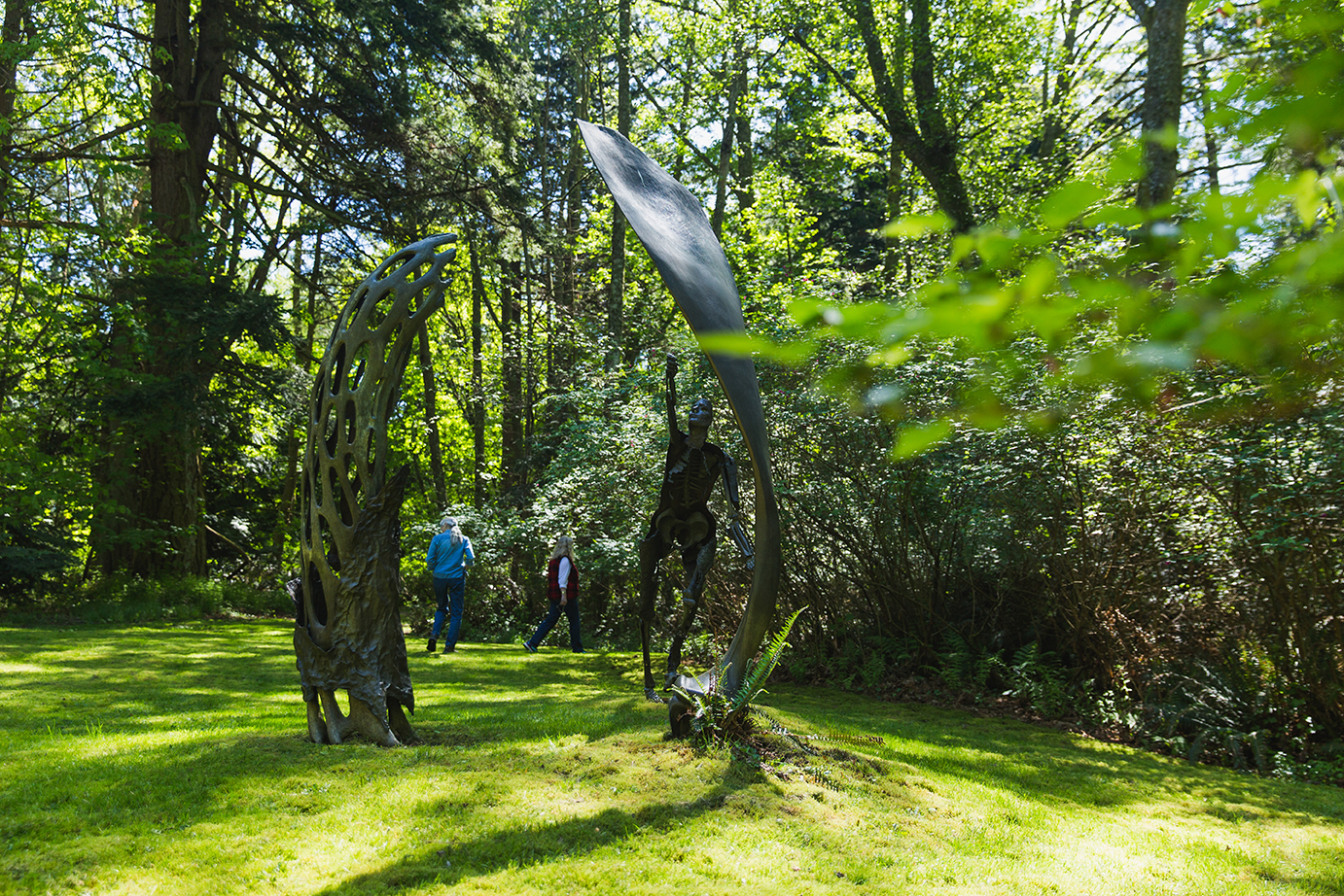 two people walk among two soaring sculptures on a lawn surrounded by tall trees