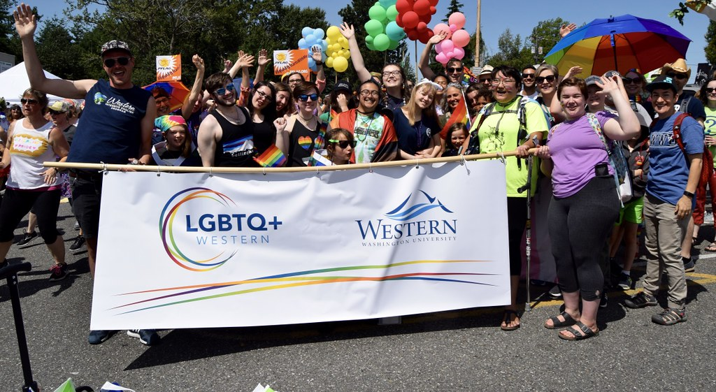 Pride parade participants gather behind a WWU banner