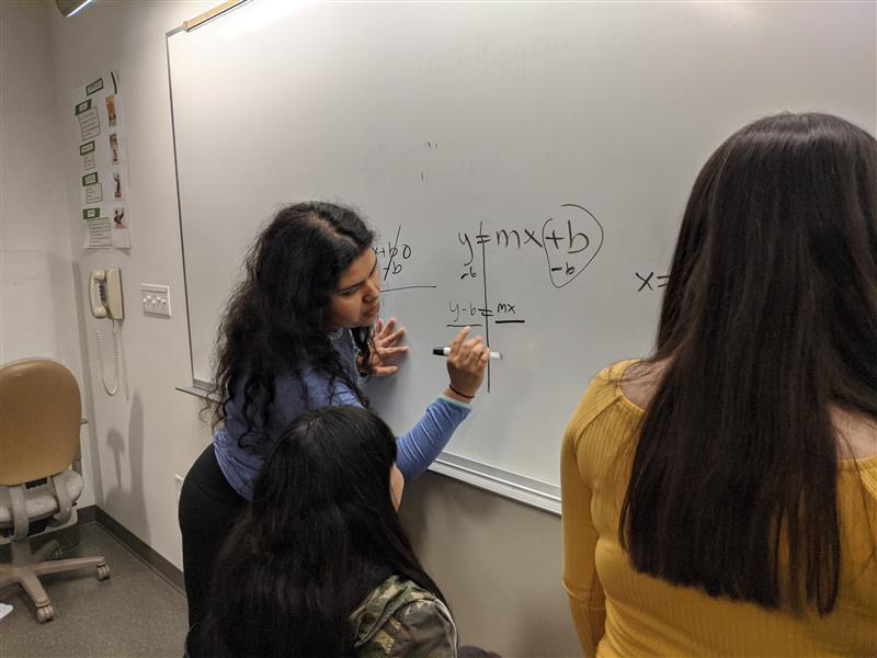 Beatriz Morales, a Biology major and lead mentor for Compass 2 Campus, works on a math problem earlier in the school year with one of the students she mentors.
