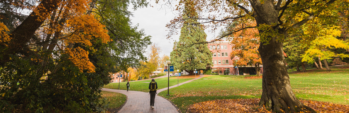 Fall comes to the Old Main lawn as leaves turn and students walk to and from class