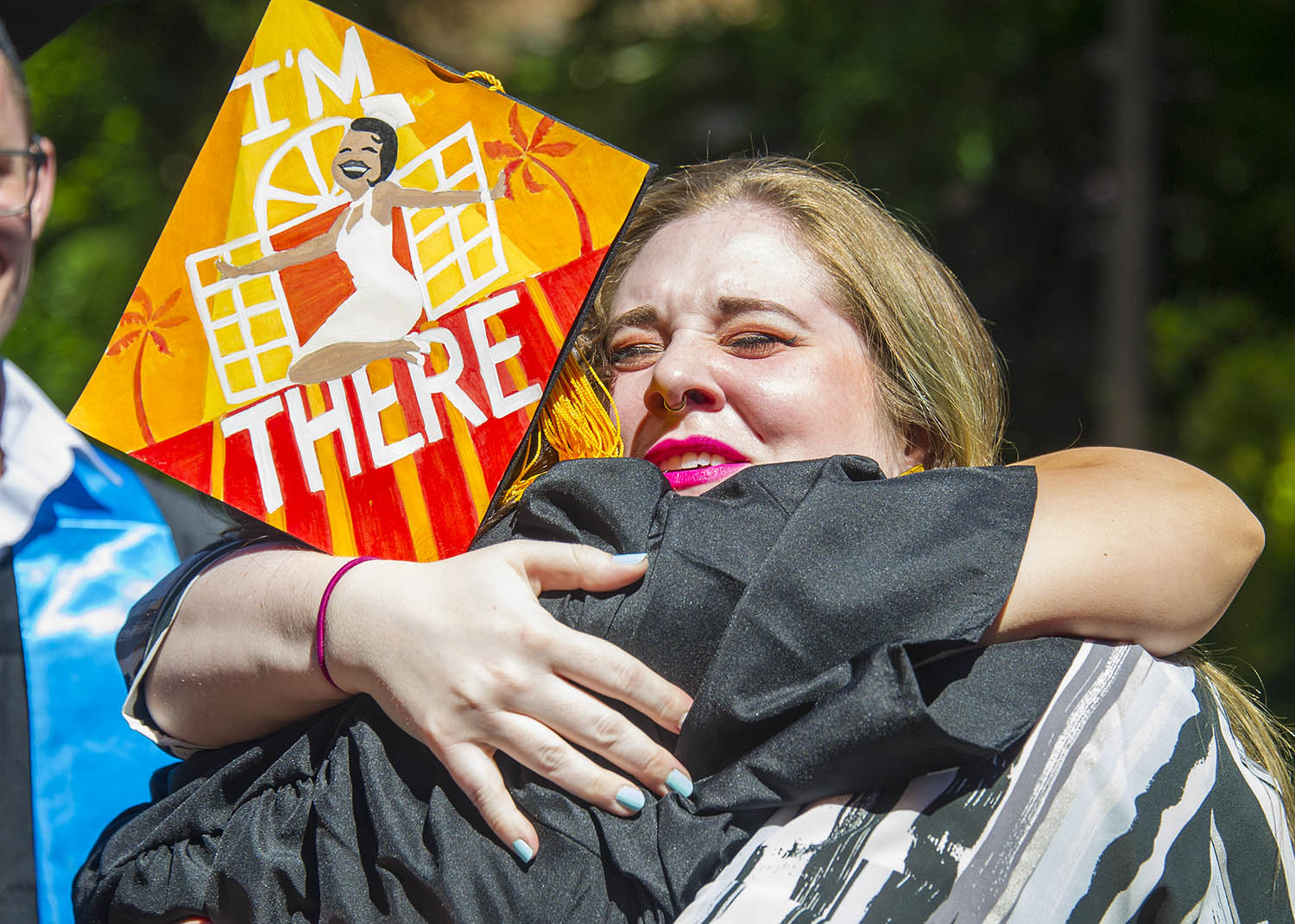 A student hugging another student with a decorated cap and gown.