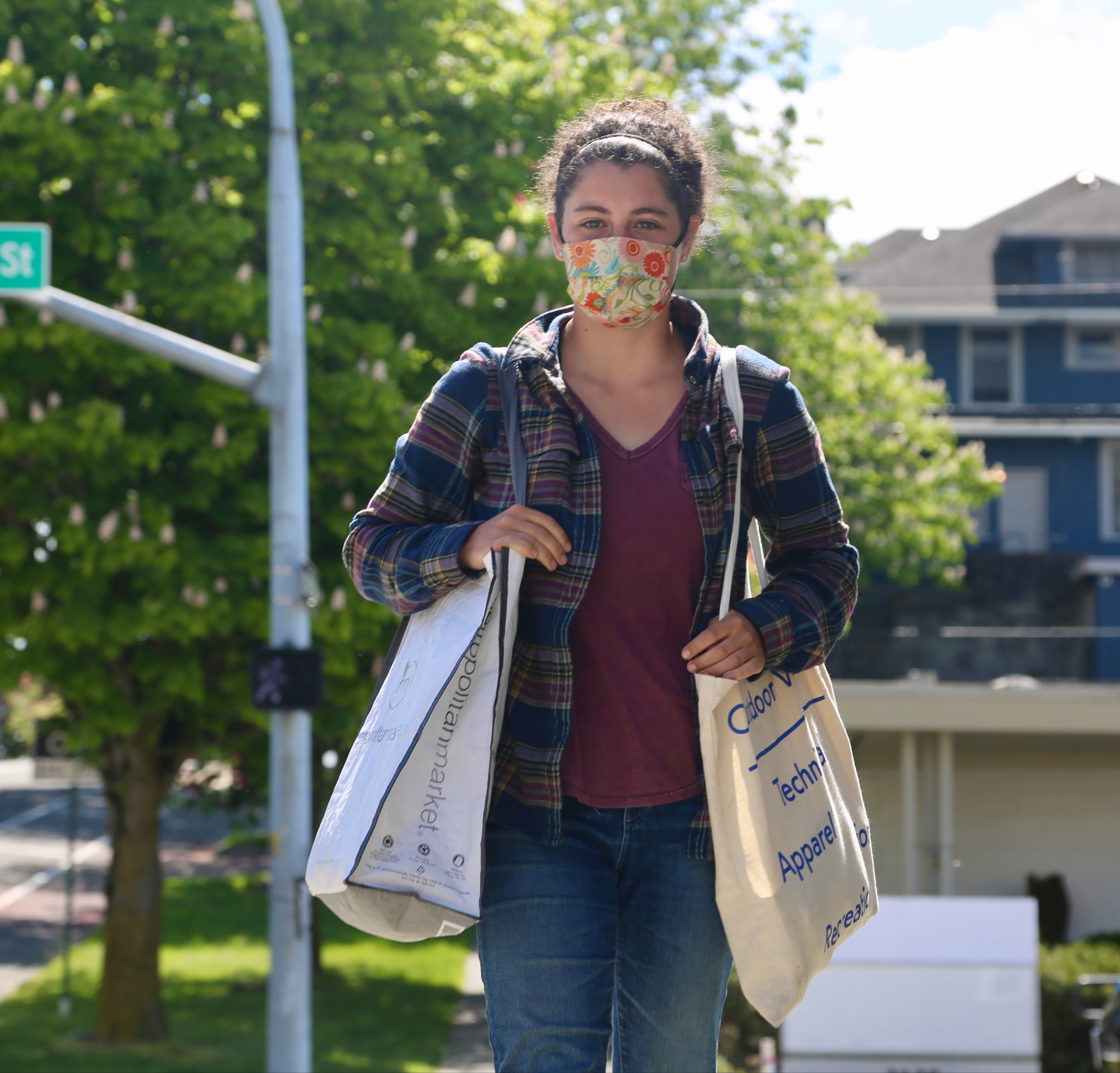 student wearing a mask walks home after food shopping at the co-op