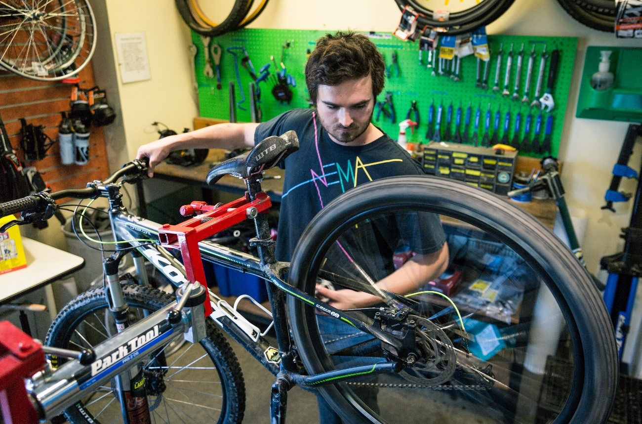 At WWUs outdoor Center, students have access to tools. One student stands in front a bike on a stand, fixing it.