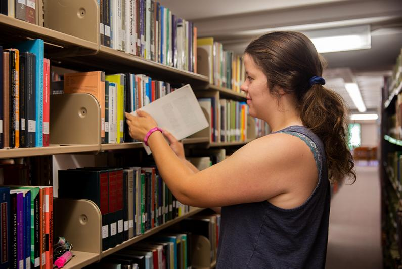 Western Senior Ashley Koeffler looking for a book in Wilson Library on August 6, 2019.