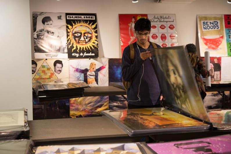 Srvejm Chaudhau browses through posters on the final day of the back to school poster sale in the Viking Union Gallery on. Sept 27.