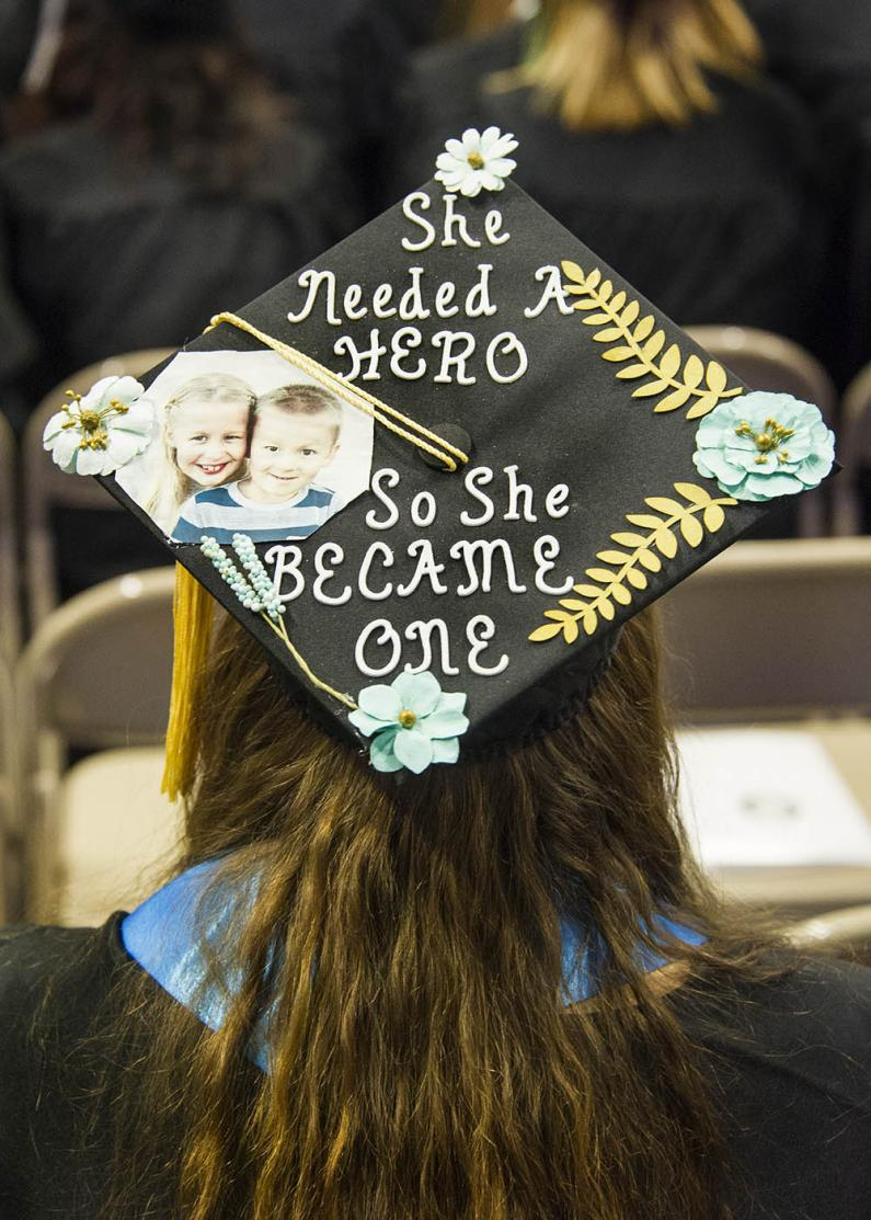 "student's mortar board states ""she needed a hero so she became one"""