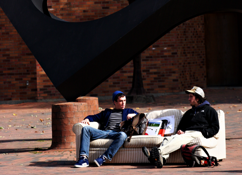 Western Washington University students Derek McFaul, left, a kinesiology major, and Robert Hamlin, a history major, chat on a couch in Red Square. The sun that these two were enjoying appears to be gone for a while, with forecasters predicting rain and hi