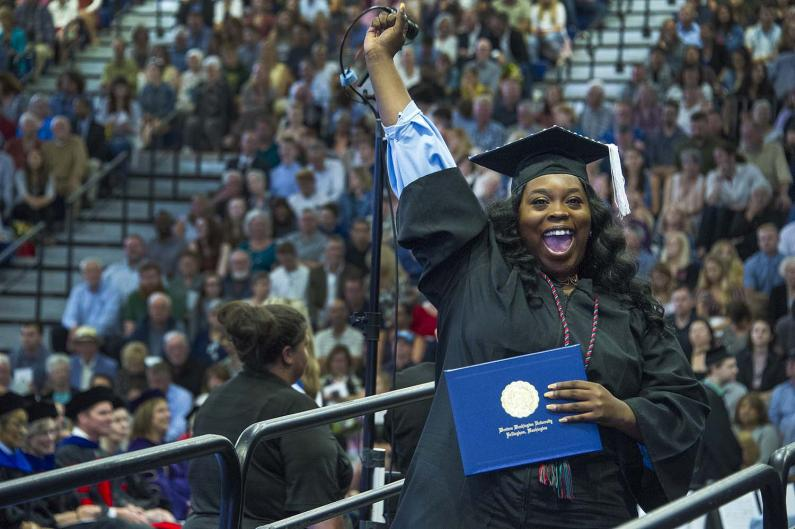 Woman smiling and holding her hand up while holding diploma holder